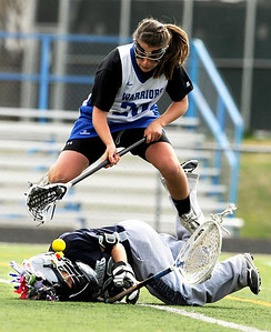 Centaurus High School junior Emma Lazaroff jumps over Columbine goalkeeper Jenna Hofmann as she goes for the ball on Saturday, April 23, during a lacrosse game against Columbine at Centaurus High School. Centaurus won the game 20-12. For more photos go to www.dailycamera.com Jeremy Papasso/ Camera
