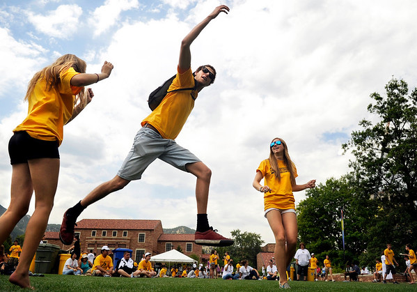 Global Jam001.JPG University of Colorado freshman Isaac Jansens, middle, dances with freshman Naomi Touchet, left, and Marlee Little, right, while a band was playing on Friday, Aug. 19, during the Global Jam at Farrand Field on the University of Colorado campus in Boulder. <br /> Jeremy Papasso/ Camera