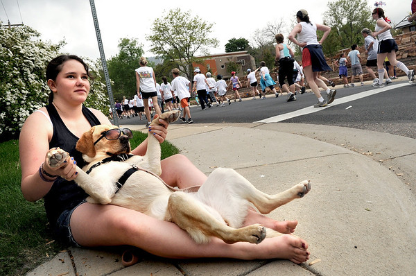 "Mallory Tomsyek, 13, of Boulder, and her dog Molly watch the runners as they pass by during the Bolder Boulder 10K Race on Monday, May 30, in Boulder. For more photos and video of the Bolder Boulder go to  <a href=""http://www.dailycamera.com"">http://www.dailycamera.com</a><br /> Jeremy Papasso/ Camera"