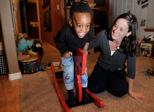 """Suzanne Schmidt and her two-year-old son Gavin laugh while he rocks on his rocking horse on Friday, Jan. 14, at their home in North Boulder. Schmidt adopted Gavin from Haiti and gave him a loving home in Boulder. For a video of the Schmidts go to  <a href=""""http://www.dailycamera.com"""">http://www.dailycamera.com</a><br /> Photo by Jeremy Papasso"""