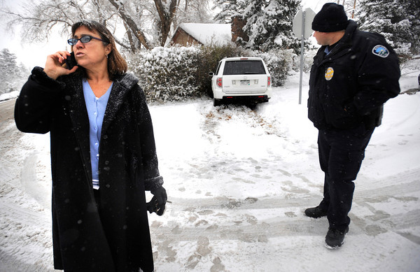 SNOW7.jpg Juciene Wilk makes a phone call as Accident Investigator Officer Mike Mogan looks over the scene of a slide off in Boulder on Thursday morning. Wilk said a car stopped in front of her as she came 9th Street. <br /> She said she drove off the road and sheared off a fire hydrant to avoid hitting the vehicle in front of her.<br /> Photo by Paul Aiken The Camera