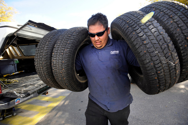 SNOWTIRE2.jpg Mark Aguirre, of Peerless Tires in Boulder, carries four snow tires at a time during an busy day at the shop as customers lined-up to have snow tires put on their vehicles in advance of a predicted snow storm this week.<br /> Photo by Paul Aiken Monday Oct 24, 2011