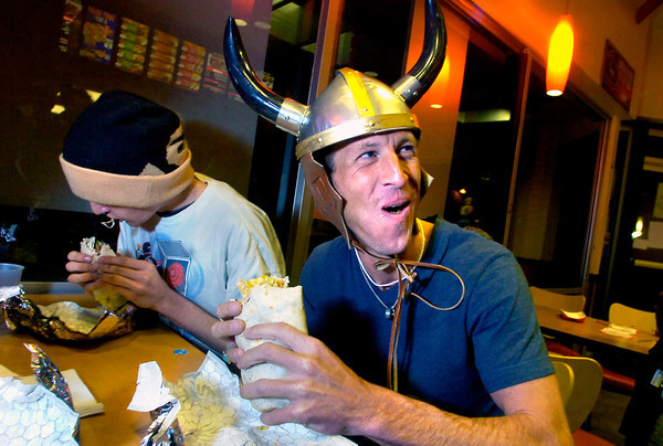 "EATCONTEST212.JPG Todd Roe, wearing a viking helmet, digs into a large ""Macho"" burrito during a timed eating contest on Friday night at the Del Taco on University Hill in Boulder.  Roe,  who couldn't put the burrito away in the two minute time frame, ended up on the restaurant's Wall of Shame.<br /> For a video of the contest go to  <a href=""http://www.dailycamera.com"">http://www.dailycamera.com</a><br /> Photo by Paul Aiken / March 4, 2011"