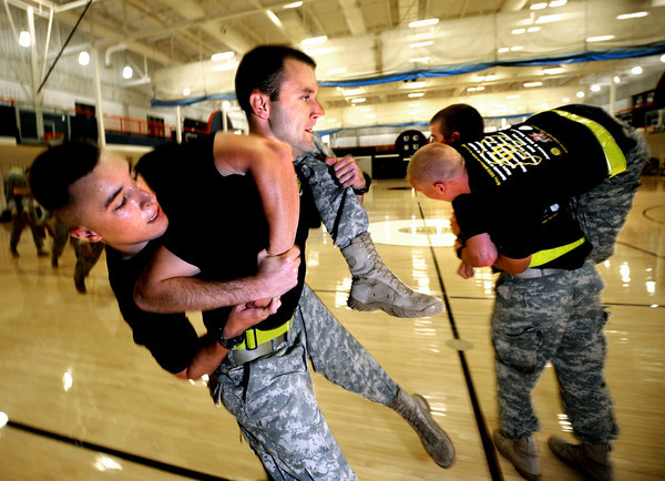 """ROTC169.JPG Cadet Captain Max Perez carries third year Cadet Robert-Josef Heitzer as the Alpha Company, Golden Buffalo Battalion trains very  early Thursday morning on September 8, 2011 in the CU recreation center on the University of Colorado Boulder Campus.<br /> FOR MORE PHOTOS AND A VIDEO OF THE TRAINING GO TO  <a href=""""http://WWW.DAILYCAMERA.COM"""">http://WWW.DAILYCAMERA.COM</a><br /> Photo by Paul Aiken / The Camera / September 6 2011"""