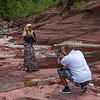 Man taking picture of a woman, Red Rock Canyon Parkway, Waterton Lakes National Park, Alberta, Canada