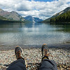 View of a person's feet with a lake and mountain range in the background, Waterton Lake, Waterton-Glacier International Peace Park, Waterton Lakes National Park, Alberta, Canada