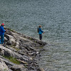 Tourists fishing at lakeshore, Crandell Lake, Waterton Lakes National Park, Alberta, Canada