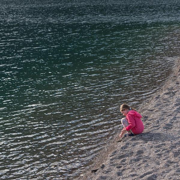 Girl sitting on shoreline of Crandell Lake, Waterton Lakes National Park, Alberta, Canada