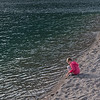 Girl sitting on shoreline of Crandell Lake, Waterton Lakes National Park, Alberta, Canada
