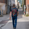 Rear view of man walking in alley, Nelson, British Columbia, Canada