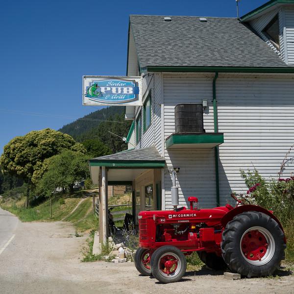 Tractor parked next to a pub, Sirdar, Near Creston, British Columbia, Canada