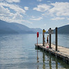 Tourists standing on pier in lake, Slocan Lake, Slocan Park, British Columbia, Canada