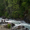 People sitting by white rapids flowing through rocks, Riondel, British Columbia, Canada