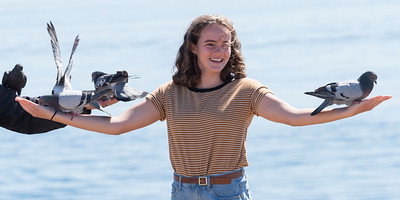 Young woman holding pigeons on her arms, Victoria, Vancouver Island, British Columbia, Canada