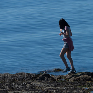 Woman walking on rocks along shoreline, Victoria, Vancouver Island, British Columbia, Canada