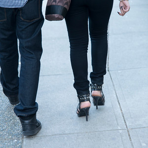 Low section view of a couple walking on street, Vancouver, British Columbia, Canada