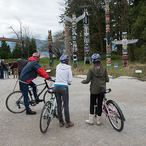 Cyclists viewing totem poles at Stanley Park, Vancouver, British Columbia, Canada