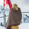 Woman standing in snow with Canadian flag waving behind her, Whistler, British Columbia, Canada