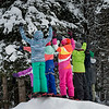 Children raising hands in front of snow covered trees, Lake Louise, Banff National Park, Alberta, Canada
