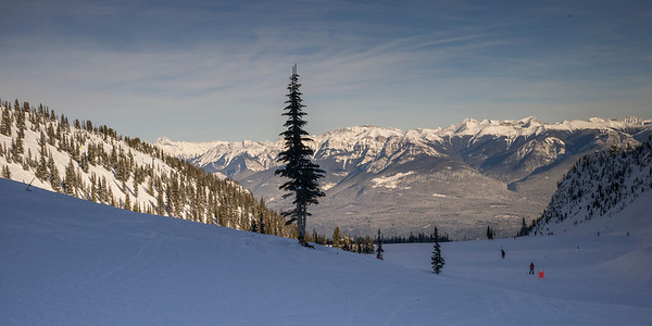 Tourists skiing in snow covered valley,  Kicking Horse Mountain Resort, Golden, British Columbia, Canada