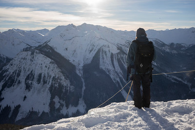 Hiker on snowcapped mountain in valley,  Kicking Horse Mountain Resort, Golden, British Columbia, Canada