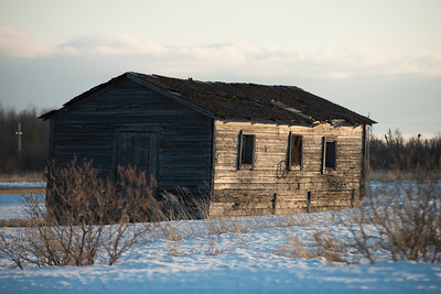 Log cabin in snow covered field at Hecla Grindstone Provincial Park, Manitoba, Canada