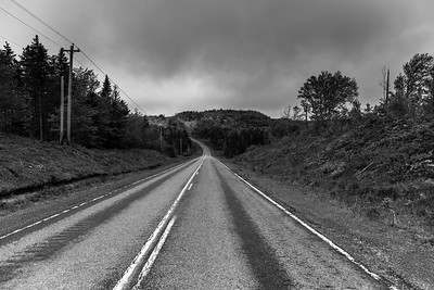 Empty road passing through rural landscape, St. Peter's, Cape Breton Island, Nova Scotia, Canada