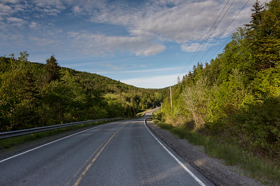 Empty road amidst trees by hills, Ceilidh Trail, Cape Breton Island, Nova Scotia, Canada