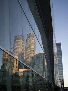Low angle view of glass building exterior with reflection of skyscrapers, Toronto, Ontario, Canada
