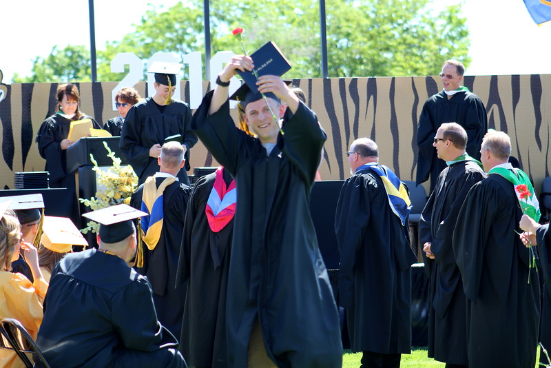 A grad show off his diploma and flower at commencement.