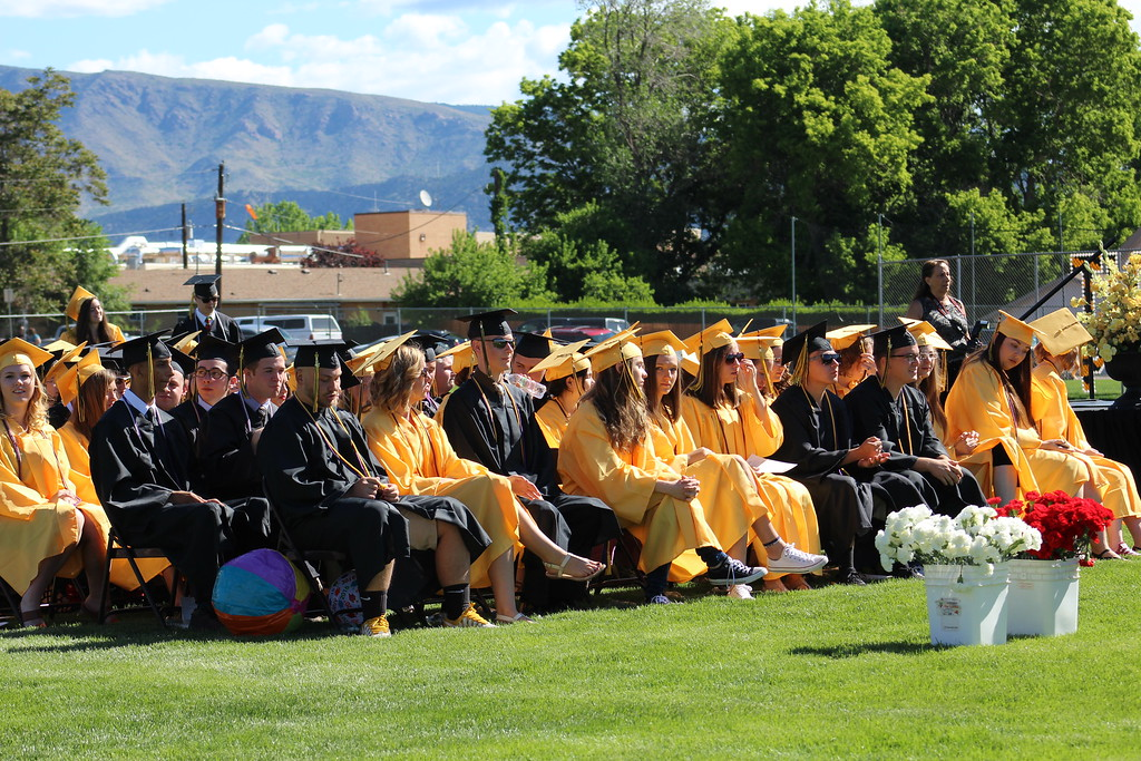 . Half of the school\'s 216 graduates sit on the field at Citizens\' Stadium before receiving their diplomas.