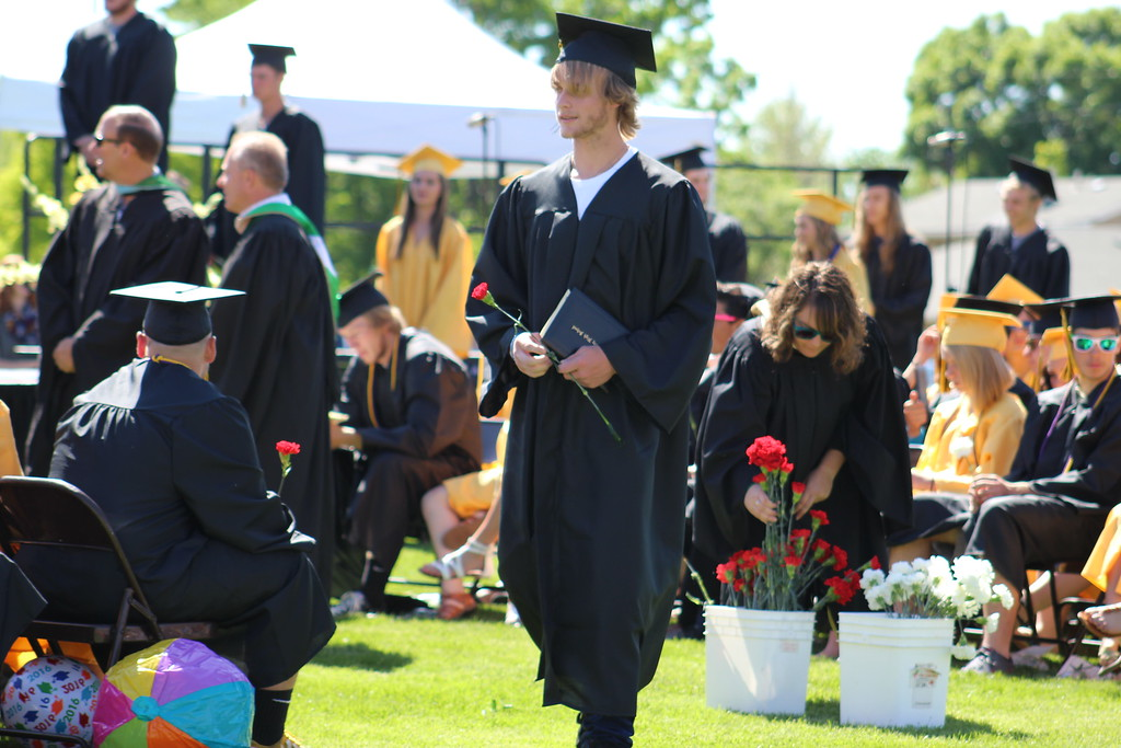 . A grad holds onto his diploma and a flower.