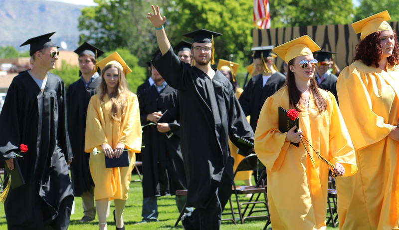 A grad waves to the crowd as the ceremony wraps up.