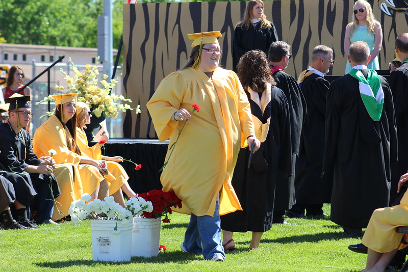 A grad accepts a flower after receiving her diploma.