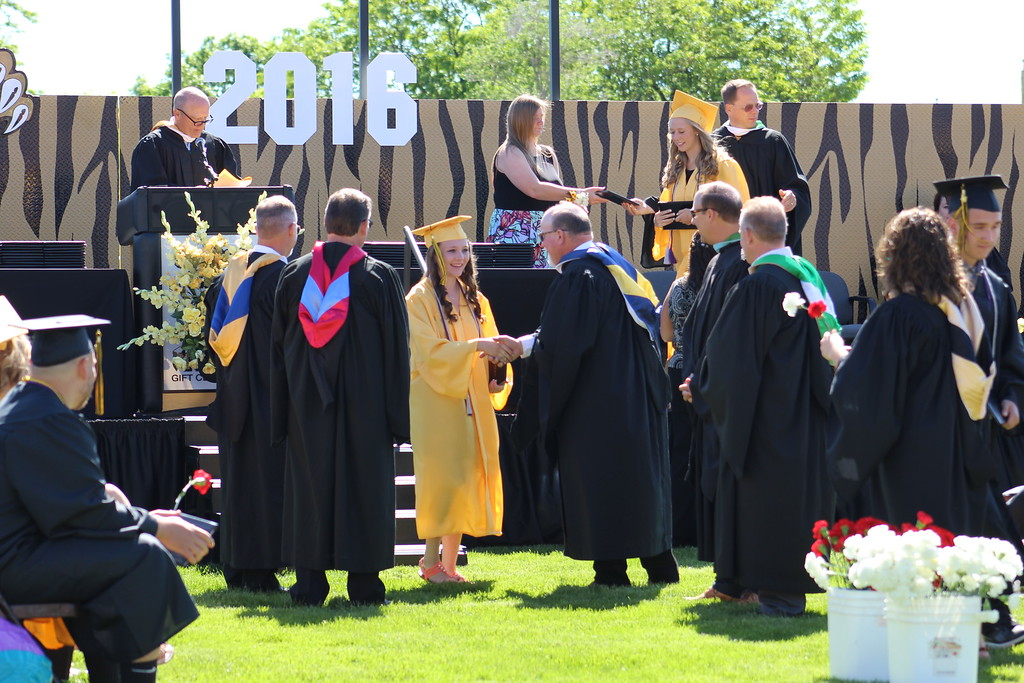 . An administrator greets a new CCHS grad after she accepts her diploma.