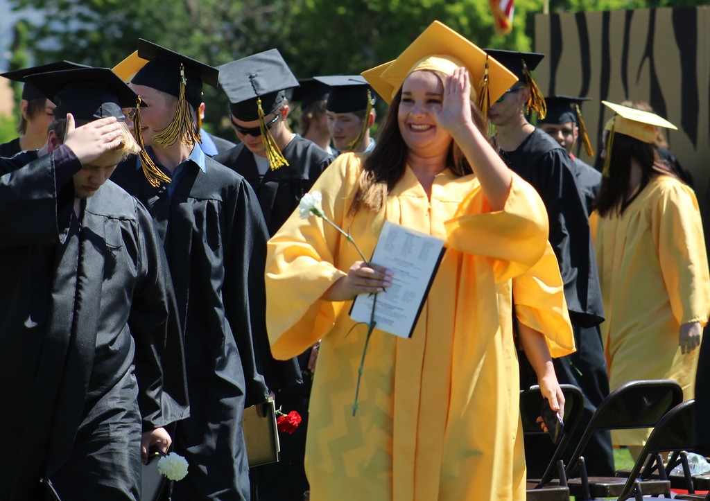 . A grad waves to the crowd at Citizens\' Stadium.