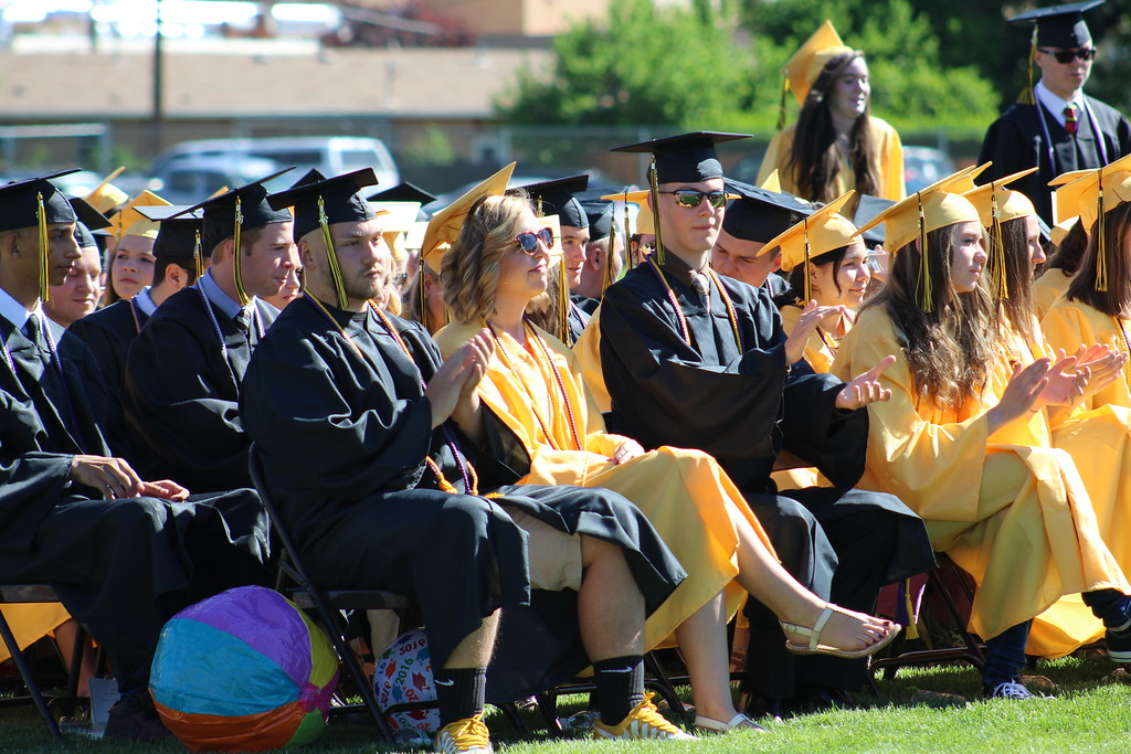 . Graduates clap after hearing a speech by the school\'s head boy, Zachary Manchester.