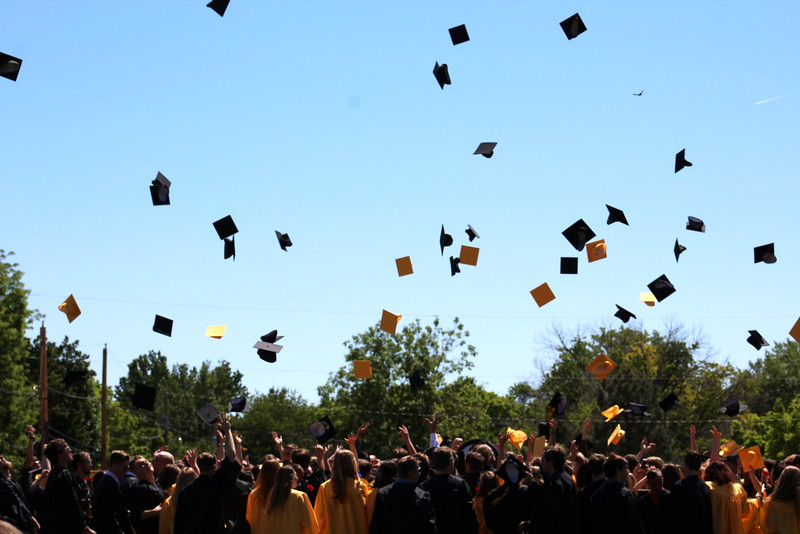Graduates toss their caps at the end of the ceremony.