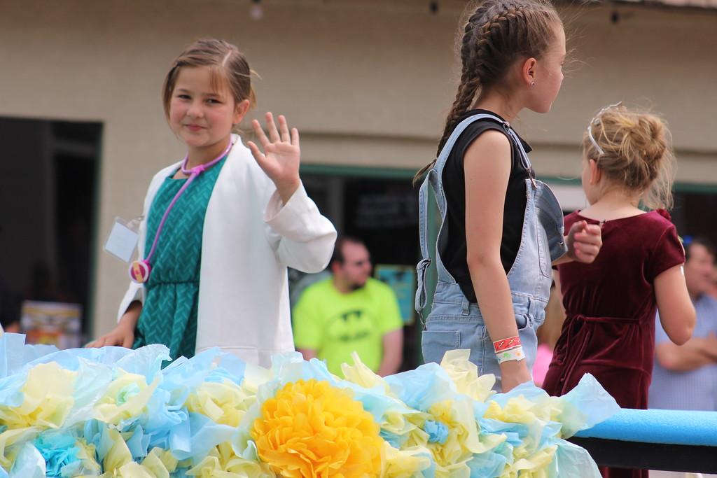. A Women of Gratitude float member rides along Saturday through the 2017 Blossom Festival Parade.