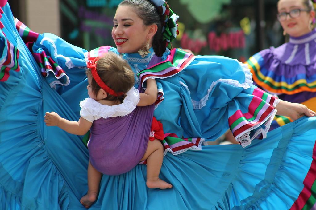 . A parade member rides along with an El Alazan dancer Saturday through the 2017 Blossom Festival Parade.