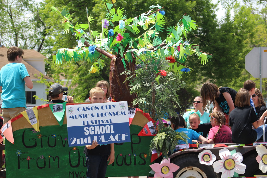 . Mountain View Core Knowledge School student Adam Kimmick hold up a sign Saturday in front of the school\'s second-place float. Lincoln School of Science and Technology won first place in the category.