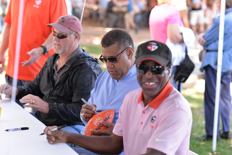Denver Broncos alumni sign autographs at a festival following the Pioneer Day Parade.