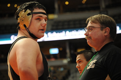 Tigers junior Garrett Benell talks with coaches Duff Seaney, front, and Erik Ortega during an injury timeout on Friday at the Class 4A state wrestling tournament at Pepsi Center in Denver. Brandon Hopper/Daily Record