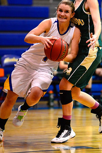 Husky junior Carly Chaney, left, drives to the basket Friday January 11, 2013 against Manitou Springs' Ali Thompson in Florence. Jeff Shane/ Daily Record