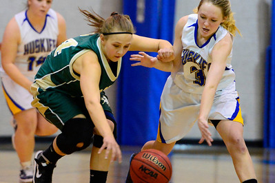 Husky junior Megan Droll, right, goes after a ball Friday January 11, 2013 against Manitou Springs' Gabby Santos in Florence. Jeff Shane/ Daily Record