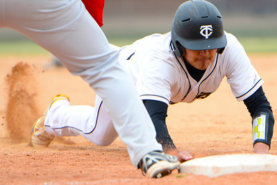 Tigers senior RJ Stainbrook dives back to first base against Pueblo Centennial at Justin Field. Jeff Shane/ Daily Record