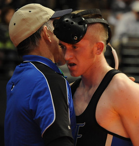Jacob Yslas is consoled by coach Craig Addington after his second-round consolation match on Friday during the Class 3A state wrestling tournament at Pepsi Center in Denver. Brandon Hopper/Daily Record