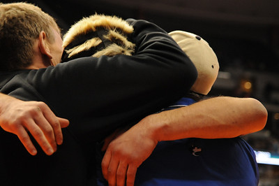 Coaches Bob Masse, left, and Craig Addington embrace Scott Sandoval after his semifinal win on Friday at Pepsi Center in Denver. Brandon Hopper/Daily Record