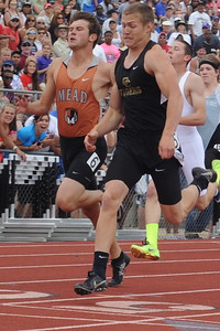 Tigers senior Zac McCoy crosses the finish line in the 200-meter race ahead of Mead's Alex Mead as Christine Conley and Andrea Tuck (left) cheer him on. Brandon Hopper/Daily Record