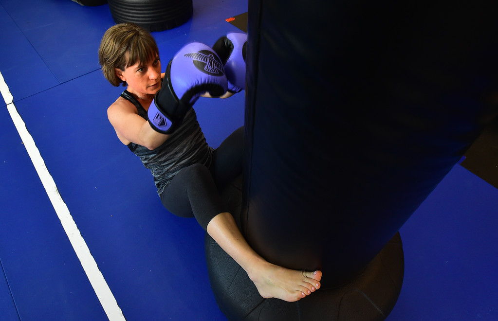 . Theresa Pelser performs sit ups in the Adult Cardio Kickboxing class at Schilz Martial Arts in Lafayette on Monday. For more photos go to dailycamera.com Paul Aiken Staff Photographer March 12, 2018.